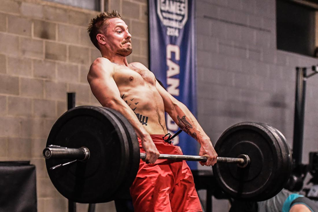 Male athlete pulls barbell in heavy clean attempt