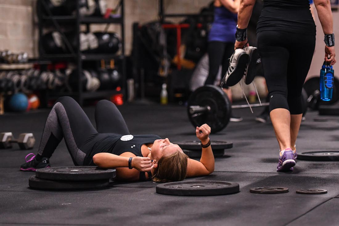 Athlete lies sweaty and exhausted on gym floor