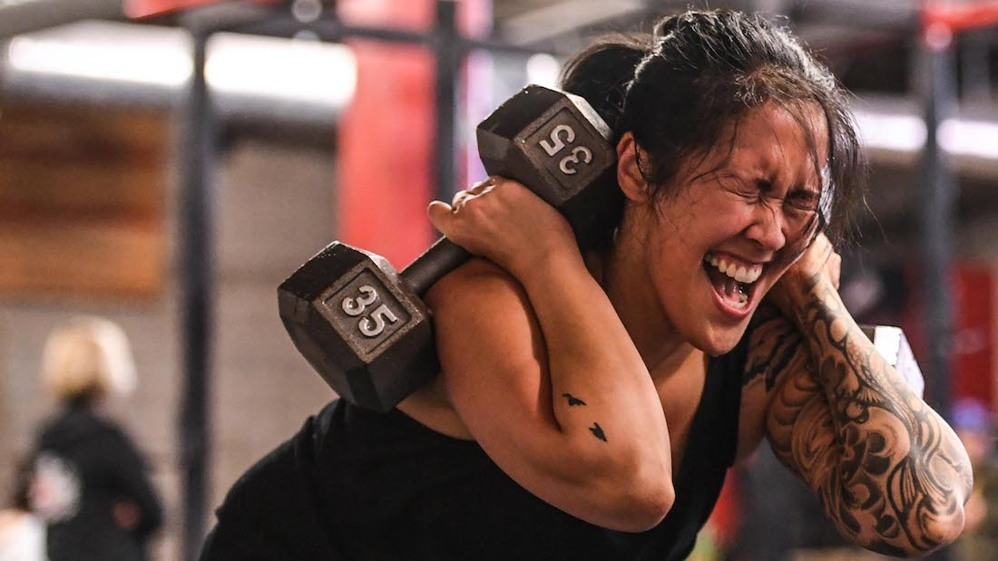 Grimacing woman squats with two 35-lb. dumbbells