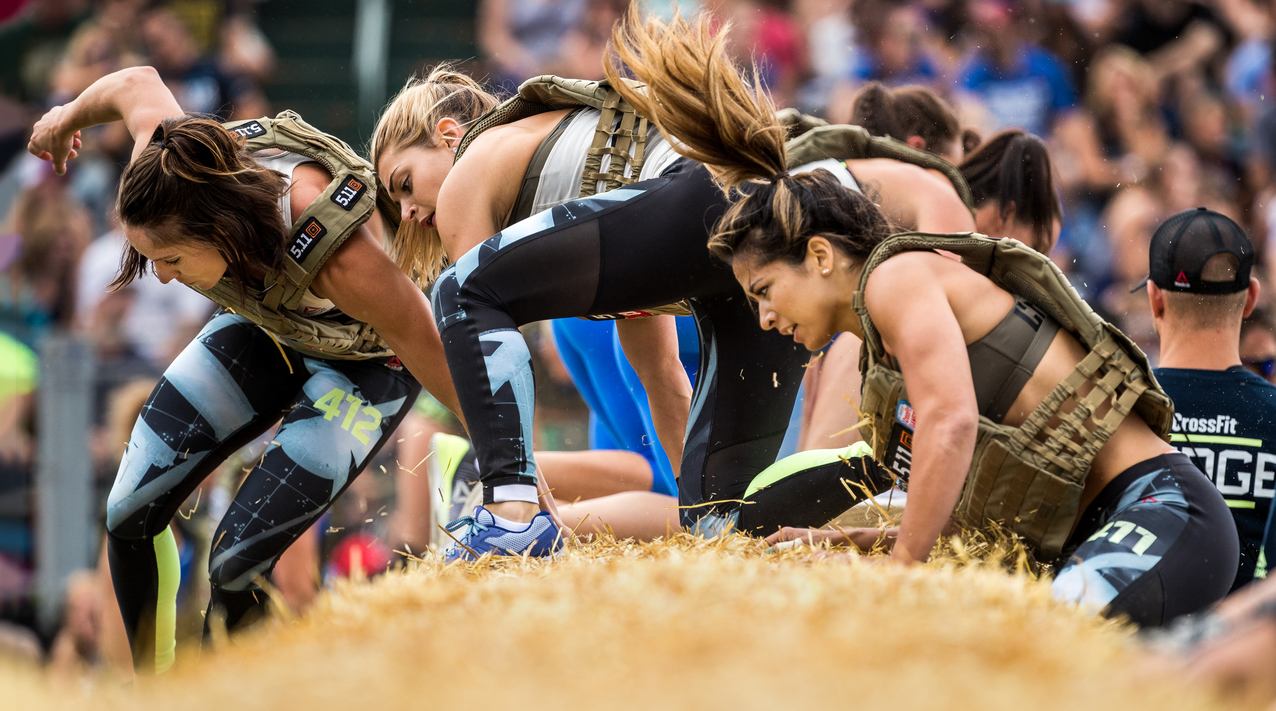 Team athletes maneuver over hay bales at the 2017 Reebok CrossFit Games
