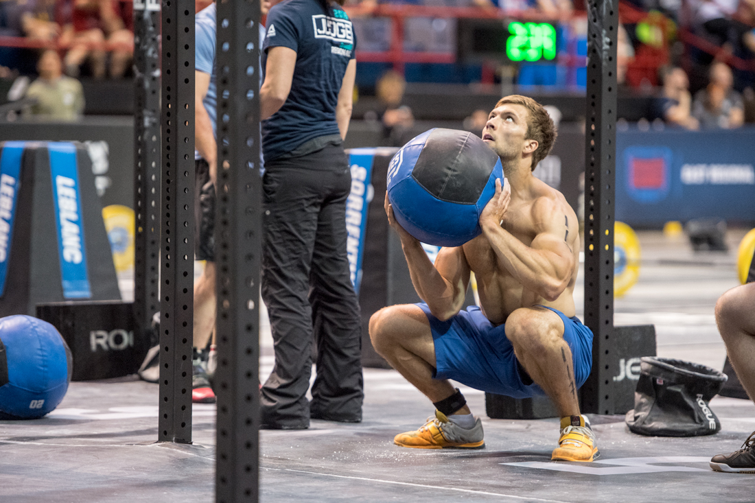 Alexandre Caron squatting with a wall ball.