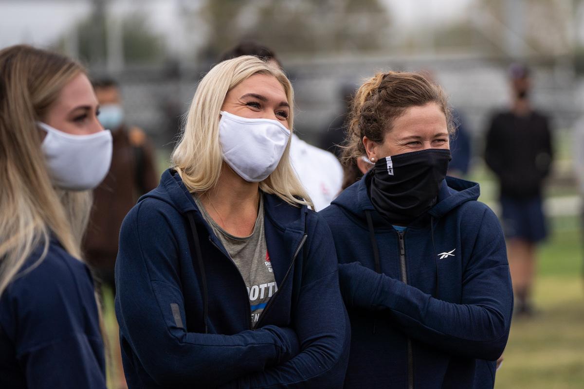 Women competitors wear masks along the sidelines