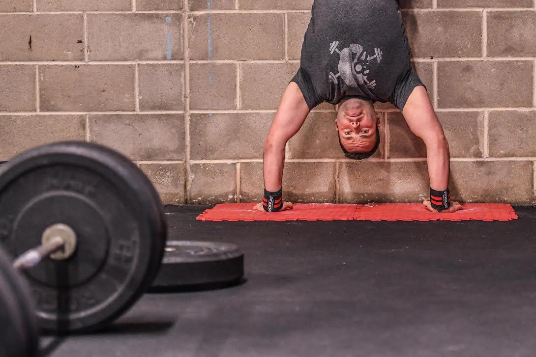 Inverted athlete pressing into HSPU