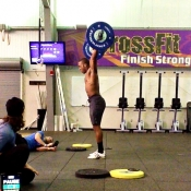 Barbell overhead position. The barbell must come to full lockout overhead with the hips, knees and arms fully extended, and the bar directly over the heels.