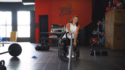 Rebecca pulling a sled in her wheelchair