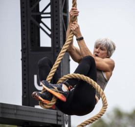 Masters woman climbing rope